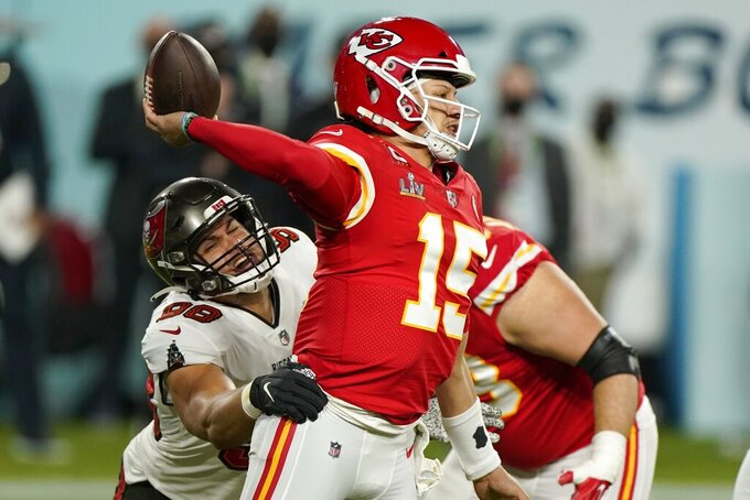 Kansas City Chiefs quarterback Patrick Mahomes throws a pass as he is pressured by Tampa Bay Buccaneers outside linebacker Anthony Nelson, left, during the first half of the NFL Super Bowl 55 football game Sunday, Feb. 7, 2021, in Tampa, Fla. (AP Photo/Gregory Bull)