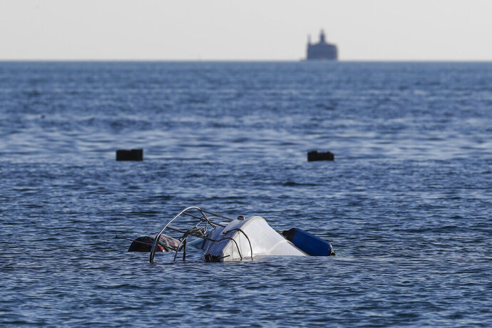 A boat remains upside down in the water south of West Fullerton Parkway at the lakefront in Chicago, Thursday, July 11, 2019. Authorities say one person died and two were rescued after the sailboat capsized early Thursday in Lake Michigan. (Jose M. Osorio/Chicago Tribune via AP)