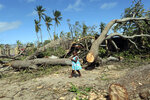 A young girl walks past trees uprooted by Cyclone Kenneth when it struck Ibo island north of Pemba city in Mozambique, Wednesday, May, 1, 2019. The government has said more than 40 people have died after the cyclone made landfall on Thursday, and the humanitarian situation in Pemba and other areas is dire. More than 22 inches (55 centimeters) of rain have fallen in Pemba since Kenneth arrived just six weeks after Cyclone Idai tore into central Mozambique. (AP Photo/Tsvangirayi Mukwazhi)