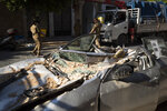Lebanese army soldiers hold aid boxes past a destroyed car near the scene of last week's explosion that hit the seaport of Beirut, Lebanon, Wednesday, Aug. 12, 2020. (AP Photo/Hassan Ammar)