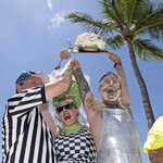 In this photo provided by the Florida Keys News Bureau, David Johnson, right, hoists his first-place trophy after he beat 24 other contestants at the Mile-High Key Lime Pie Eatin' Contest Thursday, July 4, 2019, in Key West, Fla. Johnson consumed a 9-inch Key lime pie in 58.2 seconds. The competition, billed as a sweeter alternative to New York's July 4th hotdog-eating clash, kicked off Key West's Key Lime Festival that continues through Sunday, July 7. (Rob O'Neal/Florida Keys News Bureau via AP)