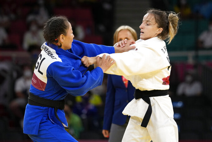 Urantsetseg Munkhbat of Mongolia, left, and Distria Krasniqi of Kosovo compete during their women's -48kg semifinal judo match at the 2020 Summer Olympics, Saturday, July 24, 2021, in Tokyo, Japan. (AP Photo/Vincent Thian)