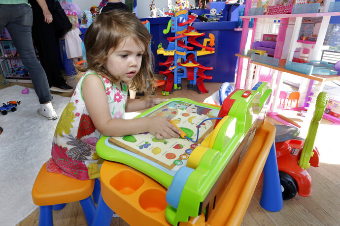 """In this Aug. 30, 2018, photo Seraphina, 3, plays with a V-Tech Explore and Write Activity Set at the Walmart Toy Shop event in New York. Walmart says 30 percent of its holiday toy assortment will be new. It will also offer 40 percent more toys on Walmart.com from a year ago. In November and December, the company's toy area will be rebranded as """"America's Best Toy Shop."""" (AP Photo/Richard Drew)"""