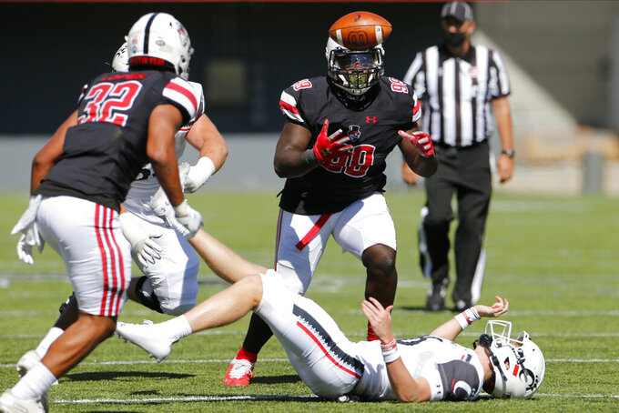 Austin Peay defensive lineman Terrell Allen, top, grabs a fumble away from Cincinnati quarterback Michael Lindauer during the second half of an NCAA college football game Saturday, Sept. 19, 2020, in Cincinnati, Ohio. Cincinnati beat Austin Peay 55-20. (AP Photo/Jay LaPrete)