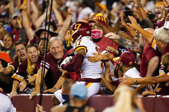 Washington Football Team wide receiver Terry McLaurin (17) jumps into the stands to celebrate his touchdown catch against the New York Giants during the first half of an NFL football game, Thursday, Sept. 16, 2021, in Landover, Md. (AP Photo/Alex Brandon)
