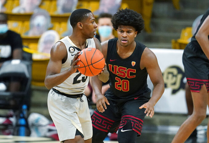 Colorado guard McKinley Wright IV, left, looks to pass the ball as Southern California guard Ethan Anderson defends during the first half of an NCAA college basketball game Thursday, Feb. 25, 2021, in Boulder, Colo. (AP Photo/David Zalubowski)