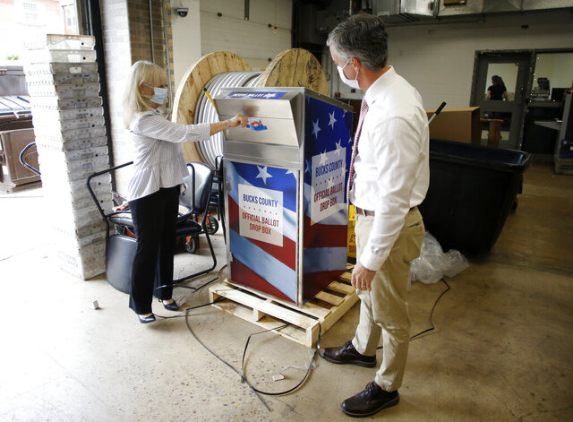 FILE - In this May 27, 2020, file photo, Bucks County commissioners Diane Ellis-Marseglia, left, and Robert Harvie unpack a new ballot drop box at the county's administration building prior to the primary election in Doylestown, Pa. With the Trump administration openly trying to undermine mail-in voting this fall, some election officials around the country are hoping to bypass the Postal Service by installing lots of ballot drop boxes in libraries, community centers and other public places. (AP Photo/Matt Slocum, File)