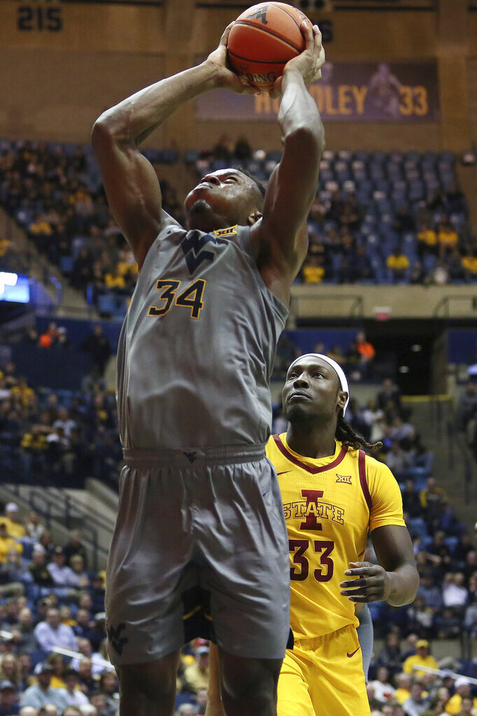 West Virginia forward Oscar Tshiebwe (34) shoots as he is defended by Iowa State forward Solomon Young (33) during the second half of an NCAA college basketball game Wednesday, Feb. 5, 2020, in Morgantown, W.Va. (AP Photo/Kathleen Batten)