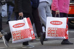 FILE - In this Nov. 29, 2019, file photo people carry shopping bags while crossing a street in San Francisco. On Thursday, Jan. 16, 2020, the Commerce Department releases U.S. retail sales data for December. (AP Photo/Jeff Chiu, File)