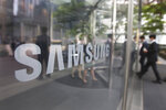 FILE - In this April 28, 2021, file photo, Employees walk past a logo of the Samsung Electronics Co. at its office in Seoul, South Korea, Wednesday, April 28, 2021. South Korea will release billionaire Lee on parole this week after he spent 18 months in prison for his role in a massive corruption scandal that triggered nationwide protests and ousted the country's previous president. (AP Photo/Ahn Young-joon, File)