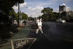 "A city worker, dressed in protective gear, sprays disinfectant as a measure to curb the spread of the new coronavirus, on the perimeters of Chapultepec Park which has reopened after being closed for several months, in Mexico City, Wednesday, July 1, 2020. On a four-color alert level, in which red is the worst and green the best, Mexico City downgraded the city's alert to ""orange"" even though it has the country's largest numbers of infections and deaths. (AP Photo/Fernando Llano)"