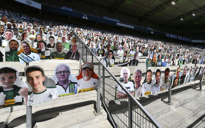 Cardboards with photos of Moenchengladbach fans displayed on the stands prior the German Bundesliga soccer match between Borussia Moenchengladbach and Union Berlin in Moenchengladbach, Germany, Sunday, May 31, 2020. The German Bundesliga becomes the world's first major soccer league to resume after a two-month suspension because of the coronavirus pandemic. (AP Photo/Martin Meissner, Pool)