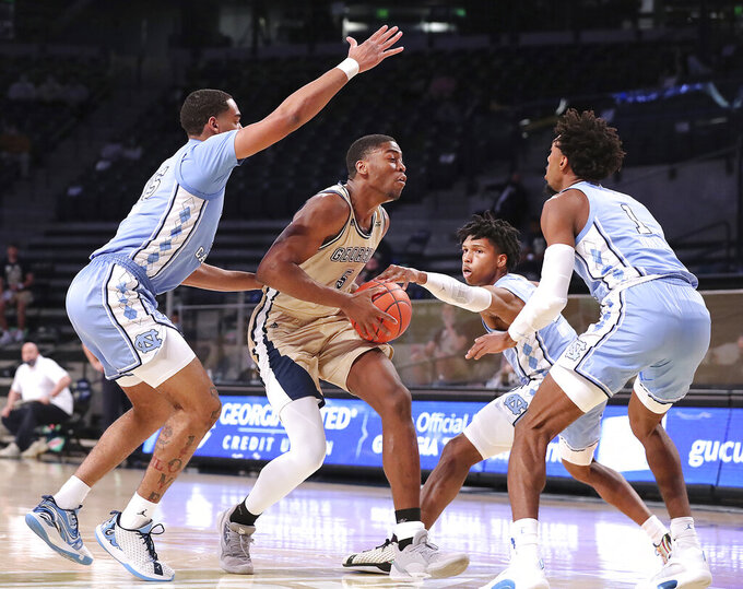 Georgia Tech forward Moses Wright is triple-teamed by North Carolina defenders Garrison Brooks, Caleb Love, and Rechon Black, from left, during the first half of an NCAA college basketball game Wednesday, Dec. 30, 2020, in Atlanta. (Curtis Compton/Atlanta Journal-Constitution via AP, Pool)