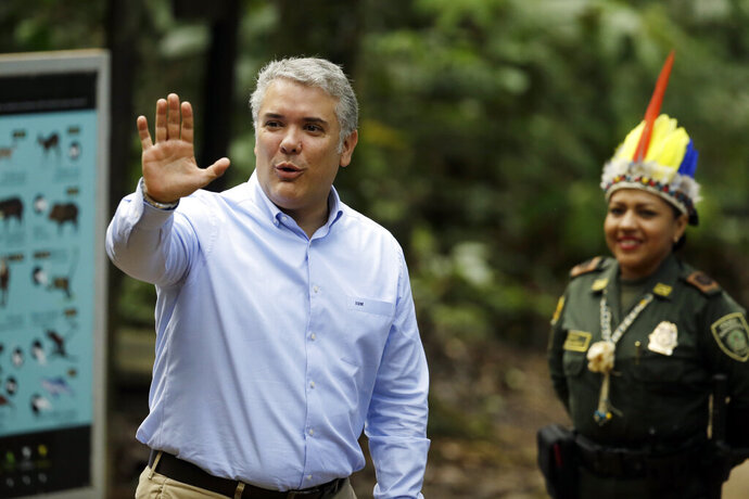 Colombia's President Ivan Duque waves upon his arrival for a meeting with leaders of several South American nations that share the Amazon, in Leticia, on Colombia's Amazon river border with Brazil and Peru, Friday, Sept. 6, 2019. Presidents and representatives from several countries in South America's Amazon region met to discuss a joint strategy for preserving the world's largest rain forest, which has been under threat from a record number of wildfires. (AP Photo/Fernando Vergara)
