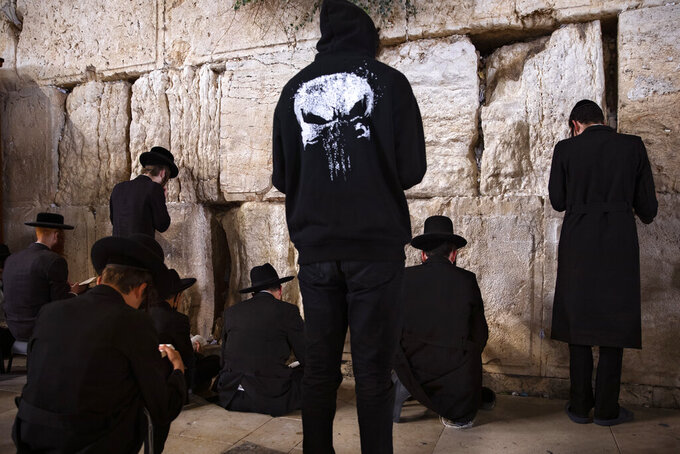 Ultra-Orthodox Jewish men pray during mourning ritual of Tisha B'Av (Ninth of Av) fasting and a memorial day, commemorating the destruction of ancient Jerusalem temples, at the Western Wall, the holiest site where Jews can pray in the Old City of Jerusalem, Sunday, July 18, 2021. (AP Photo/Oded Balilty)