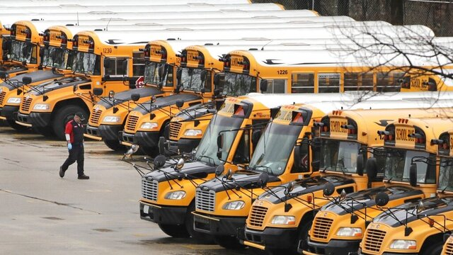 FILE - In this April 27, 2020, file photo, a worker passes public school buses parked at a depot in Manchester, N.H. As the Trump administration pushes full steam ahead to force schools to resume in-person education, public health experts warn that a one-size-fits-all reopening could drive infection and death rates even higher. (AP Photo/Charles Krupa, File)