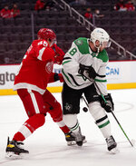 Detroit Red Wings defenseman Danny DeKeyser (65) and Dallas Stars center Jason Dickinson (18) try controlling the puck during the first period of an NHL hockey game, Saturday, March 20, 2021, in Detroit. (AP Photo/Carlos Osorio)