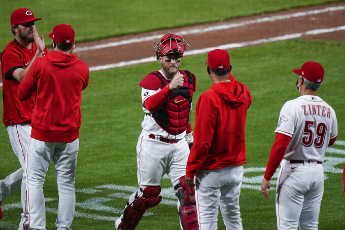 Cincinnati Reds' Cincinnati Reds' Tucker Barnhart, center,  celebrates with staff and teammates after defeating the Pittsburgh Pirates at Great American Ball Park in Cincinnati, Tuesday, April 6, 2021. (AP Photo/Bryan Woolston)