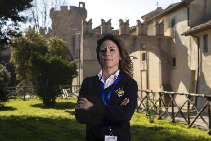 Daniela Magnanti poses in front of the Santa Severa castle, Friday, March 5, 2021 where she has a part-time work at the check-in desk of a hotel that opened in the castle. Worldwide, working women paid a high price during the pandemic as many quit jobs to care for children when schools closed. But Italy's women went into the crisis already struggling for decades to expand their presence in the national workforce. Among the 27 European Union nations, Italian women rank next to the bottom, after Greek women, in terms of percentage in national workforces. Among young women, Italians rank the lowest. (AP Photo/Alessandra Tarantino)