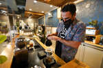 Chris Vigilante makes a dripped coffee for a customer at one of his coffee shops, Wednesday, Sept. 1, 2021, in College Park, Md. A confluence of supply chain problems, drought, frost and inflation all point to the price of your cup of morning coffee going up.  (AP Photo/Julio Cortez)