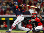 Washington Nationals' Alcides Escobar watches his solo home run in front of Cincinnati Reds catcher Tucker Barnhart during the third inning of a baseball game in Cincinnati,  Friday, Sept. 24, 2021. (AP Photo/Paul Vernon)