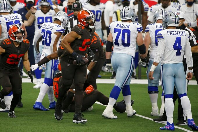 Cleveland Browns' Andrew Sendejo (23) and Olivier Vernon (54) celebrate a fumble recovery by the Dallas Cowboys as guard Zack Martin (70) and quarterback Dak Prescott (4) look on in the first half of an NFL football game in Arlington, Texas, Sunday, Oct. 4, 2020. (AP Photo/Michael Ainsworth)