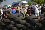 A woman makes a barricade off tyres during a protest by Nissan workers in Barcelona, Spain, Thursday, May 28, 2020. Japanese carmaker Nissan Motor Co. has decided to close its manufacturing plans in the northeastern Catalonia region, resulting in the loss of some 3,000 direct jobs. (AP Photo/Emilio Morenatti)