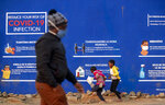 People walk past a COVID-19 advert promoting the use of face mask, washing of hands, use of sanitiser and social distance in the township of Soweto outside of Johannesburg, South Africa, Monday, July 13, 2020. South African President Cyril Ramaphosa said that top health officials warn of impending shortages of hospital beds and medical oxygen as South Africa reaches a peak of COVID-19 cases, expected between the end of July and September. South Africa's rapid increase in reported cases has made it one of the world's centers for COVID-19. (AP Photo/Themba Hadebe)