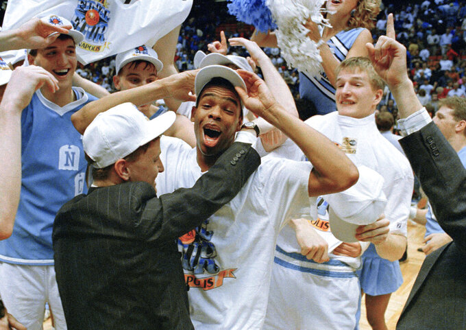 FILE - North Carolina's Hubert Davis celebrates on the court with teammates after the Tar Heels defeated Temple 75-72 in the NCAA East Regional championship game at the Meadowlands in East Rutherford, N.J., in this Sunday, March 24, 1991, file photo. Hubert Davis has the strong connection to North Carolina's storied men's basketball program as a former Tar Heels player under Dean Smith and assistant coach under Roy Williams. Now he's a first-time college head coach set to put his own touches on the UNC program.(AP Photo/Bill Kostroun)