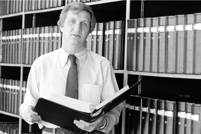 FILE - In this Jan. 8, 1976, file photo, Gil Brandt, vice president for personnel development for the Dallas Cowboys, holds one of the books of statistics he has in the Cowboy library in Dallas, Texas. Brandt will be inducted into the Pro Football Hall of Fame in Canton, Ohio on Aug. 3, 2019. (AP Photo/Greg Smith, File)