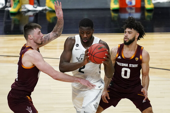Arizona State's Chris Osten, left, and Holland Woods (0) guard Oregon's Eugene Omoruyi (2) during the second half of an NCAA college basketball game in the quarterfinal round of the Pac-12 men's tournament Thursday, March 11, 2021, in Las Vegas. (AP Photo/John Locher)