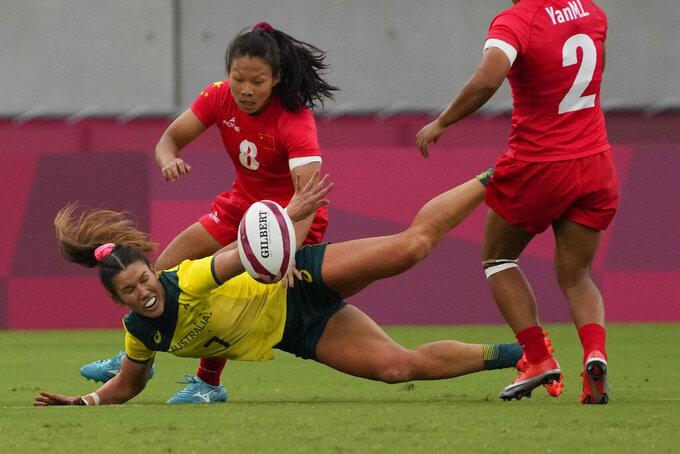 Australia's Charlotte Caslick, bottom, bales with China's Liu Xiaoqian, in their women's rugby sevens match at the 2020 Summer Olympics, Thursday, July 29, 2021 in Tokyo, Japan. (AP Photo/Shuji Kajiyama)