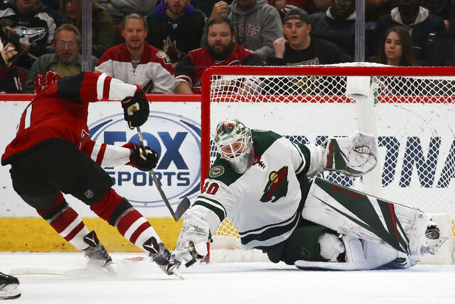 Minnesota Wild goaltender Devan Dubnyk (40) makes a save on a shot by Arizona Coyotes left wing Taylor Hall, left, during the third period of an NHL hockey game Thursday, Dec. 19, 2019, in Glendale, Ariz. The Wild won 8-5. (AP Photo/Ross D. Franklin)