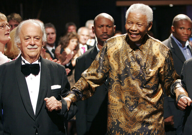 FILE — In this Wednesday Nov. 12, 2008 file photo George Bizos, left, anti-apartheid activist, and life-long friend and lawyer of Nelson Mandela, right, arrives for his 80th birthday party in Johannesburg, South Africa. Bizos has died Wednesday Sept. Sept. 9, 2020, aged 92. (AP Photo/Denis Farrell)