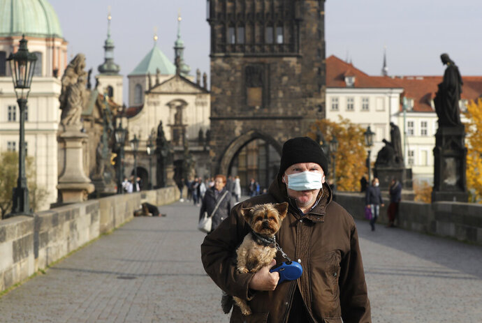 A man wearing a face mask carries his dog across the medieval Charles Bridge in Prague, Czech Republic, Wednesday, Oct. 21, 2020. In another desperate attempt to slow the rise of coronavirus infections in the Czech Republic, Health Minister Roman Prymula has announced a ban on free movement of people in the country and a closure of many stores, shopping malls and hotels. At the same time, state offices will limit their opening hours. Prime Minister Andrej Babis says those measures should prevent the collapse of the health system in early November. (AP Photo/Petr David Josek)