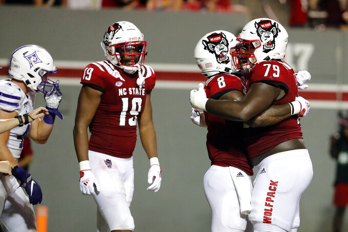 North Carolina State's Ricky Person Jr. (8) is congratulated on his touchdown by teammates Ikem Ekwonu (79) and C.J. Riley (19) during the second half of an NCAA college football game against Furman in Raleigh, N.C., Saturday, Sept. 18, 2021. (AP Photo/Karl B DeBlaker)