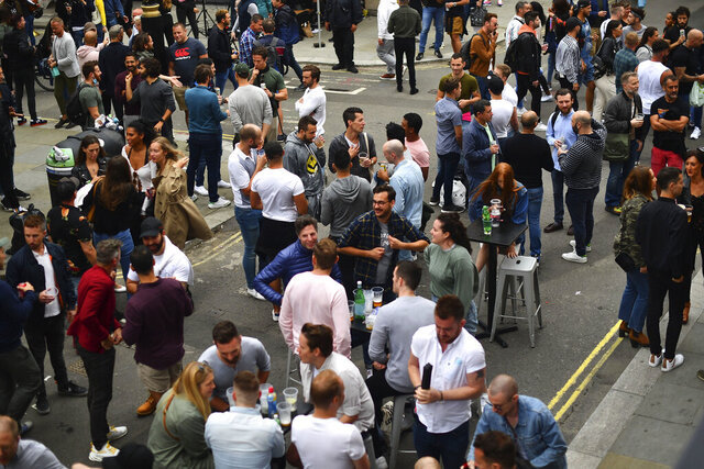 Drinkers in Soho congregate, as coronavirus lockdown restrictions eased across England, in London, Saturday July 4, 2020. England embarked on perhaps its biggest lockdown easing yet as pubs and restaurants reopened for the first time in more than three months. (Victoria Jones/PA via AP)