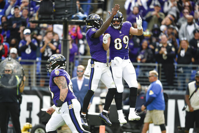 Baltimore Ravens tight end Mark Andrews (89) celebrates with quarterback Lamar Jackson, center, after they connected for a touchdown pass against the Los Angeles Chargers during the second half of an NFL football game, Sunday, Oct. 17, 2021, in Baltimore. (AP Photo/Gail Burton)