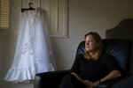 In this Wednesday, April 11, 2018, photo, Karen McDonald, whose home was swept away in a mudslide, poses for photos with her wedding veil and the underskirt to her wedding dress she had worn 35 years earlier at her wedding, in Santa Barbara, Calif. Earlier in the week, Santa Barbara resident Sarah Eglin posted on a Facebook page that she was walking along a Montecito trail with her children when they came across a zipped-up bag covered in mud and just a touch of lace sticking out. It turned out to be McDonald's long wedding veil and the underskirt of her wedding dress. (AP Photo/Jae C. Hong)
