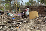 A family picks up a few items from her house which was damaged by Cyclone Kenneth when it struck Ibo island north of Pemba city in Mozambique, Wednesday, May, 1, 2019. The government has said more than 40 people have died after the cyclone made landfall on Thursday, and the humanitarian situation in Pemba and other areas is dire. More than 22 inches (55 centimeters) of rain have fallen in Pemba since Kenneth arrived just six weeks after Cyclone Idai tore into central Mozambique. (AP Photo/Tsvangirayi Mukwazhi)