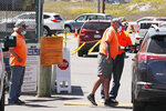 Parking attendants, wearing a protective masks due to the COVID-19 virus outbreak, check on beachgoers at the gate to Good Harbor Beach in Gloucester, Mass., Friday, May 22, 2020. Beaches in Gloucester reopened with restrictions on Friday after being closed two months ago due to the pandemic. (AP Photo/Charles Krupa)