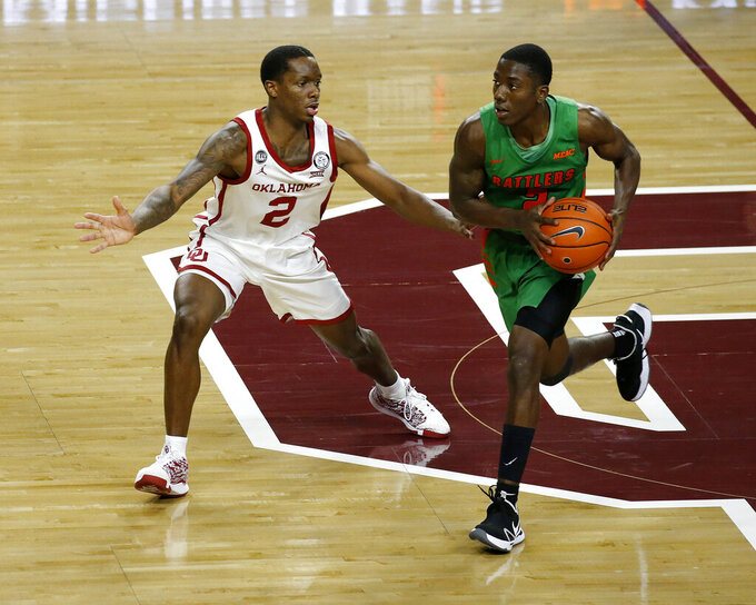 Florida A&M's Kamron Reaves, right, drives against Oklahoma's Umoja Gibson during the second half of an NCAA college basketball game in Norman, Okla., Saturday, Dec. 12, 2020. (AP Photo/Garett Fisbeck)