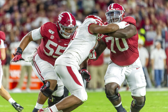 FILE - In this Oct. 26, 2019, file photo, Alabama offensive lineman Alex Leatherwood (70) blocks Arkansas defensive lineman Mataio Soli (11) as Alabama offensive lineman Emil Ekiyor Jr. (55) offers support during the first half of an NCAA college football game in Tuscaloosa, Ala. Leatherwood is likely to face his biggest challenge of the year when Alabama meets Ohio State in the national championship game on Monday, Jan. 11, 2021. (AP Photo/Vasha Hunt, File)