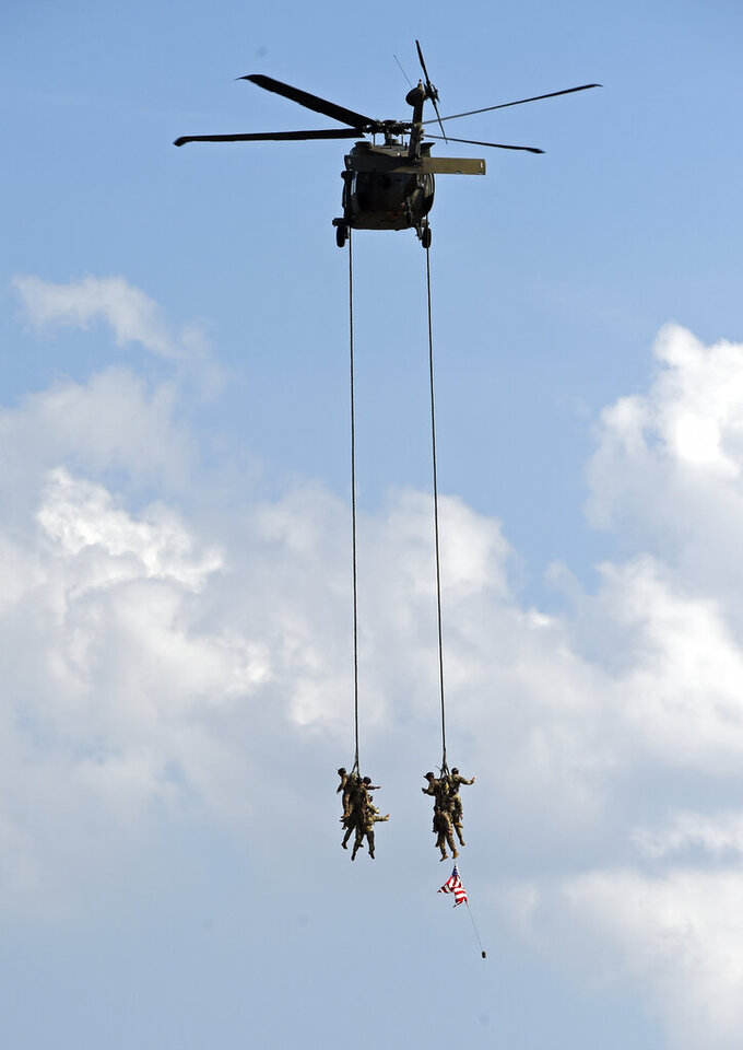 A Blackhawk helicopter carries soldiers away during activities before a NASCAR Cup Series auto race at Charlotte Motor Speedway in Concord, N.C., Sunday, May 26, 2019. (AP Photo/Mike McCarn)