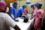 Hospital staff goes through the documents prior to COVID-19 vaccination drive at a hospital in Kolkata, India, Saturday, Jan. 16, 2021. India started inoculating health workers Saturday in what is likely the world's largest COVID-19 vaccination campaign, joining the ranks of wealthier nations where the effort is already well underway. (AP Photo/Bikas Das)
