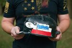 Brad Campbell holds his father Glen Campbell's hardhat at his home in Herrin, Ill., on Thursday, Oct. 11, 2018. Glen Campbell died in 2015 in an accident while driving a vehicle called a mantrip during his shift in Peabody's Gateway mine. The federal Mine Safety and Health Administration concluded that Peabody failed to maintain the mantrip in safe condition and did not have effective policies in place to protect miners.  (Neeta Satam via AP)
