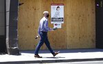A pedestrian with a takeout lunch in hand walks through an area of Scottsdale, Ariz., known for busy restaurants, bars and nightlife Tuesday, June 30, 2020, with most businesses closed for the next 30 days due to the surge in coronavirus cases in Arizona. (AP Photo/Ross D. Franklin)