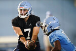North Carolina quarterback Sam Howell (7) hands off the ball to running back Ty Chandler during an NCAA college football practice in Chapel Hill, N.C., Thursday, Aug. 5, 2021. (AP Photo/Gerry Broome)