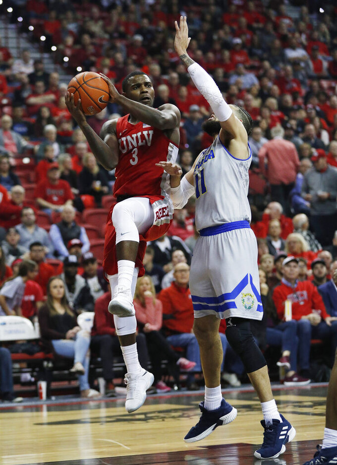 UNLV's Amauri Hardy, left, is defended by Nevada's Cody Martin during the first half of an NCAA college basketball game Tuesday, Jan. 29, 2019, in Las Vegas. (AP Photo/John Locher)
