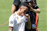 Eder Militao kisses his shirt during his official presentation after signing for Real Madrid at the Santiago Bernabeu stadium in Madrid, Spain, Wednesday, July 10, 2019. (AP Photo/Manu Fernandez)